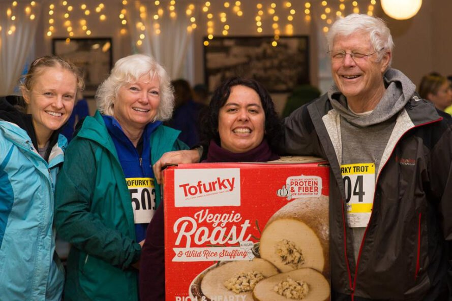 People smiling with one person wearing a cpstume that looks like a Tofurky box