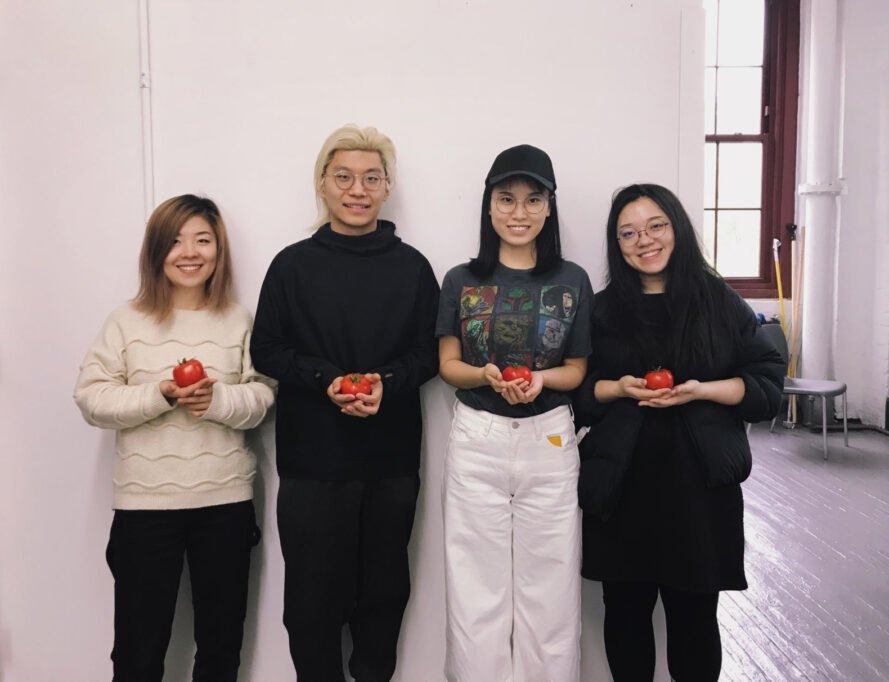 four people holding tomatoes