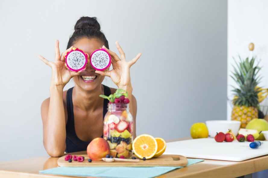 person smiling and holding dragon fruit halves over their eyes