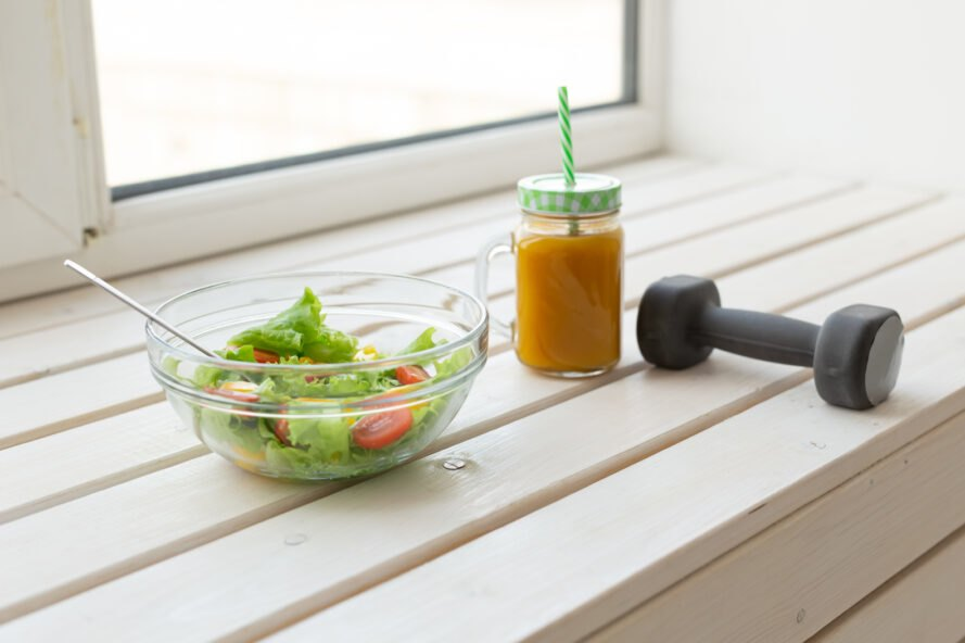salad, fruit smoothie and a dumbell on a bench