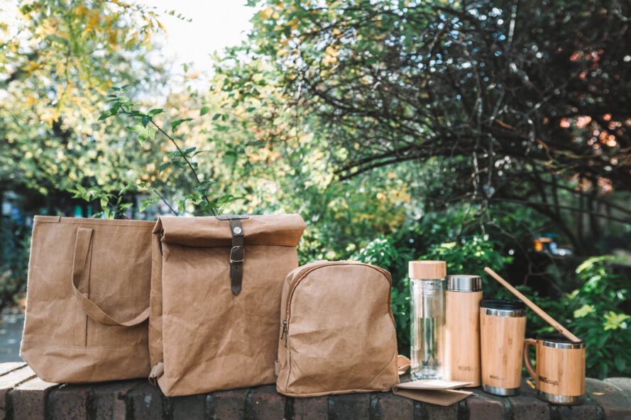 reusable bags, mugs, water bottles and utensils lined up in a row on a table outdoors