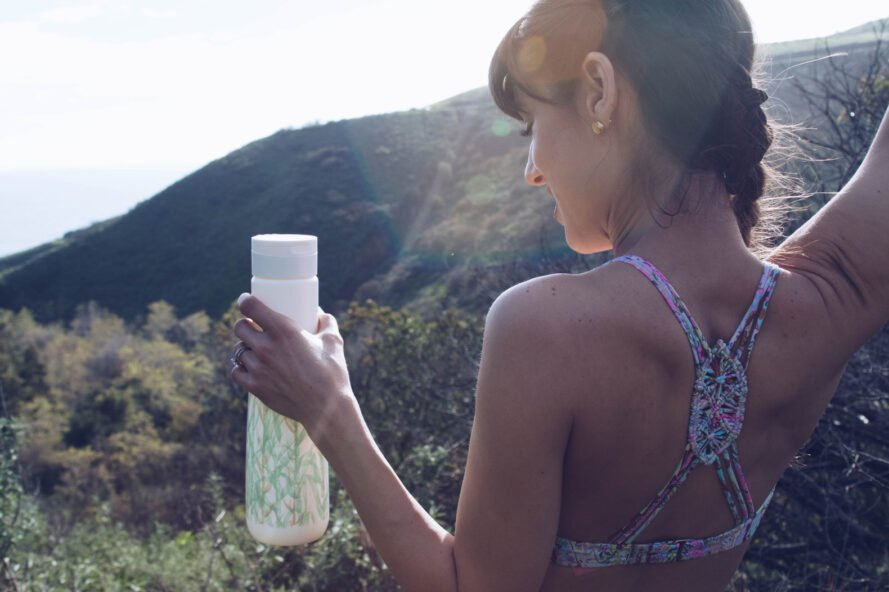 person outdoors holding white reusable water bottle with green print