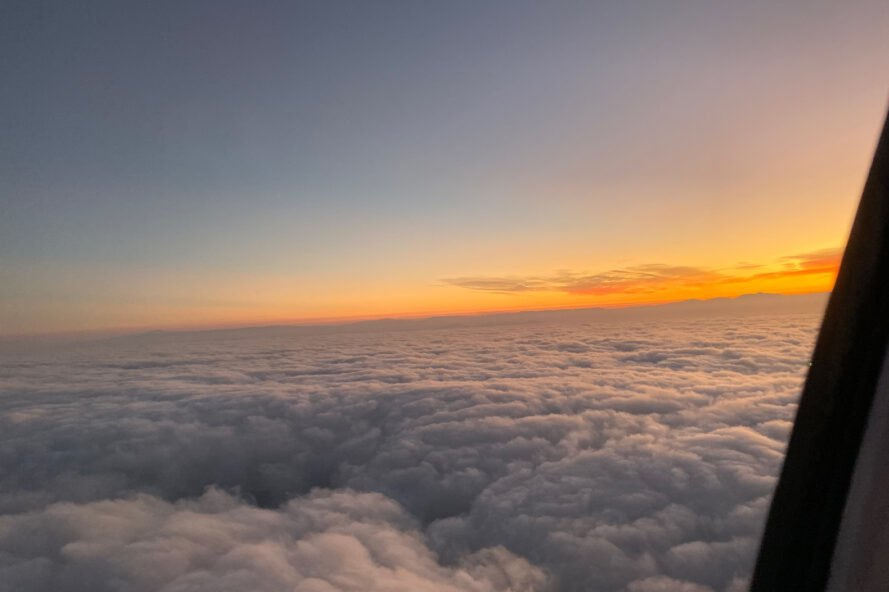 view of clouds and sunset from a plane window
