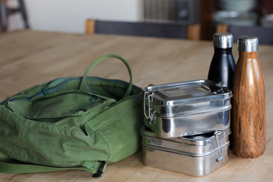 green backpack, two tin lunch boxes and a two reusable water bottles on a wood table