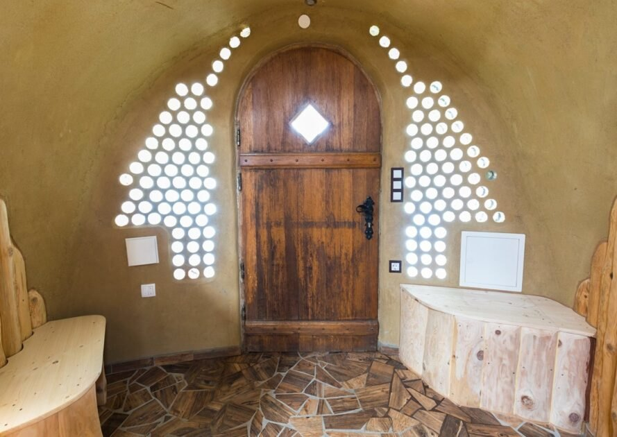 wood door surrounded by glass jars embedded in clay walls