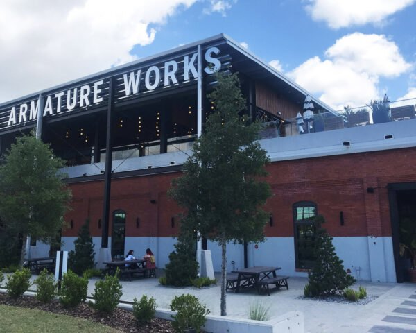 A tiered building with an Amarture Works sign and small green space in front of the building