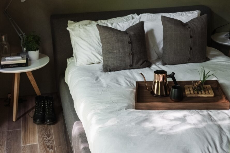 bed with two grey pillows and a coffee tray