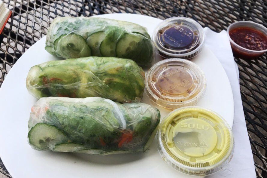 A plate with three green spring rolls and three small cups of sauces to the right, with a fourth cup of sauce on the table
