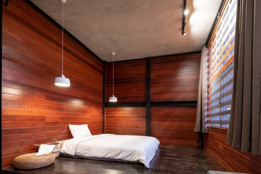 large white bed in wood-lined room