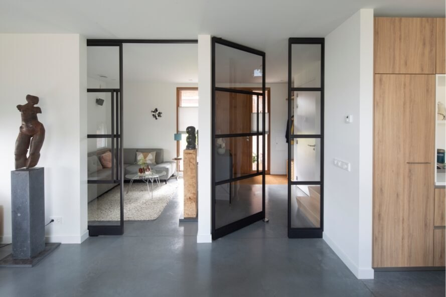 black-framed glass doors leading from living area to bedorom