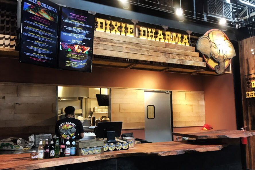 A restaurant counter with yellow lighting and the Dixie Dharma sign hanging above it, with an elephant logo to the right