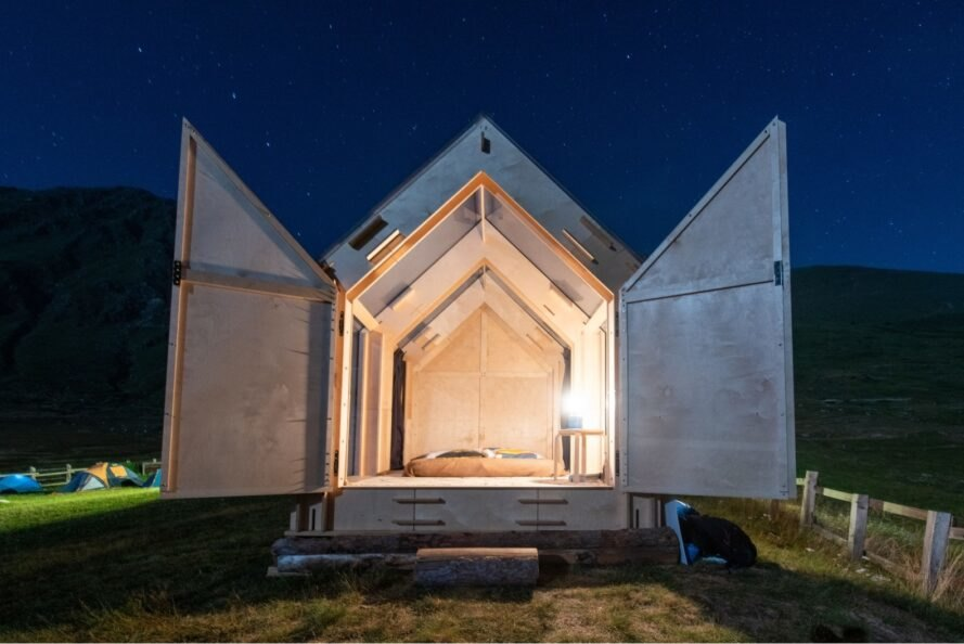 front of A-frame cabin with wood doors swung open