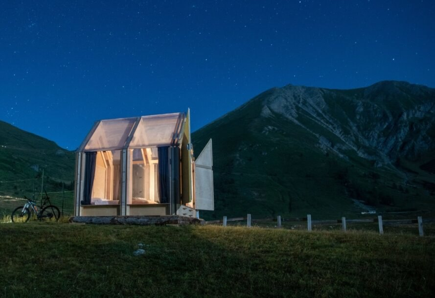 small, clear cabin lit from within at night