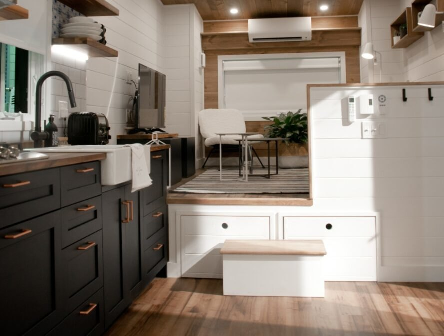 kitchen space inside tiny home with dark cabinets