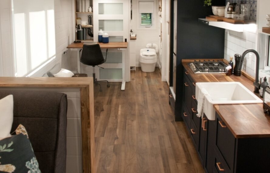 modern tiny home interior with white shiplap walls and a dark kitchen with a farmhouse sink