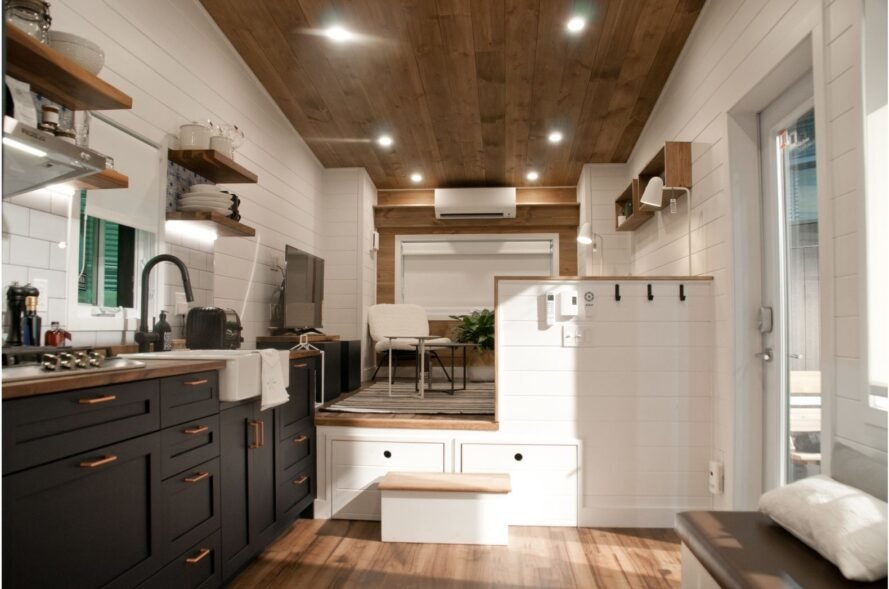 tiny home with white walls and a kitchen with black cabinetry