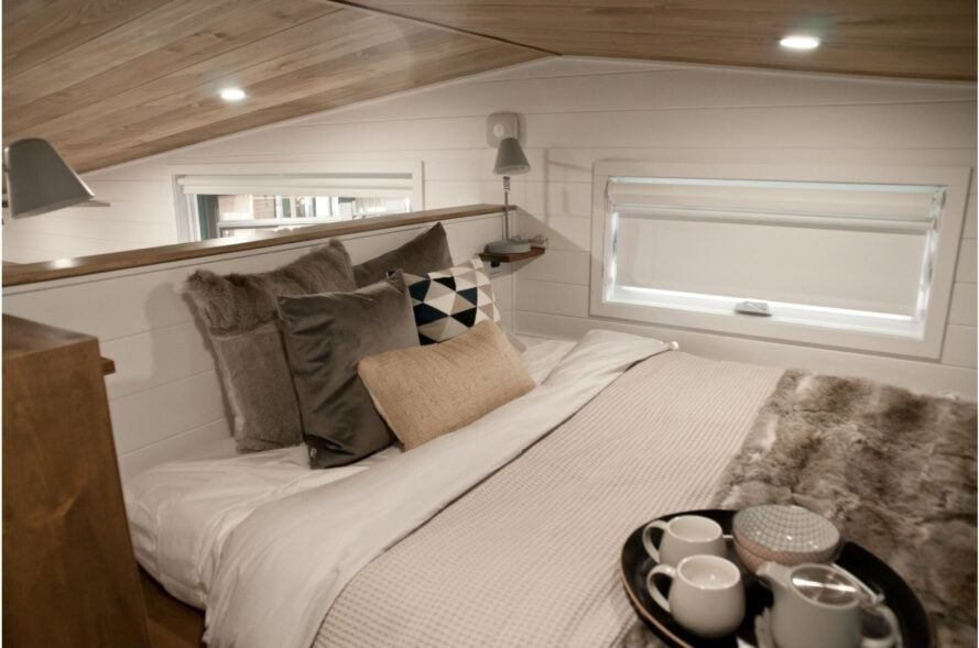 double bed with various pillows on a sleeping loft