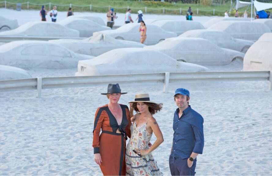 three people in front of a sand art installation