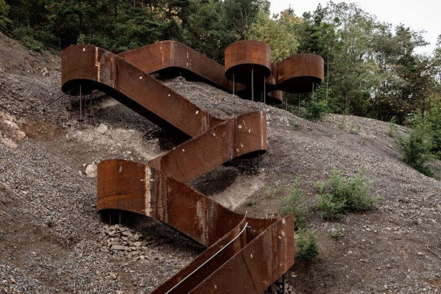 weathered steel stairs leading up a mountainside