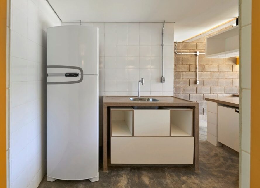 kitchen with wood counters and a tall, narrow white fridge