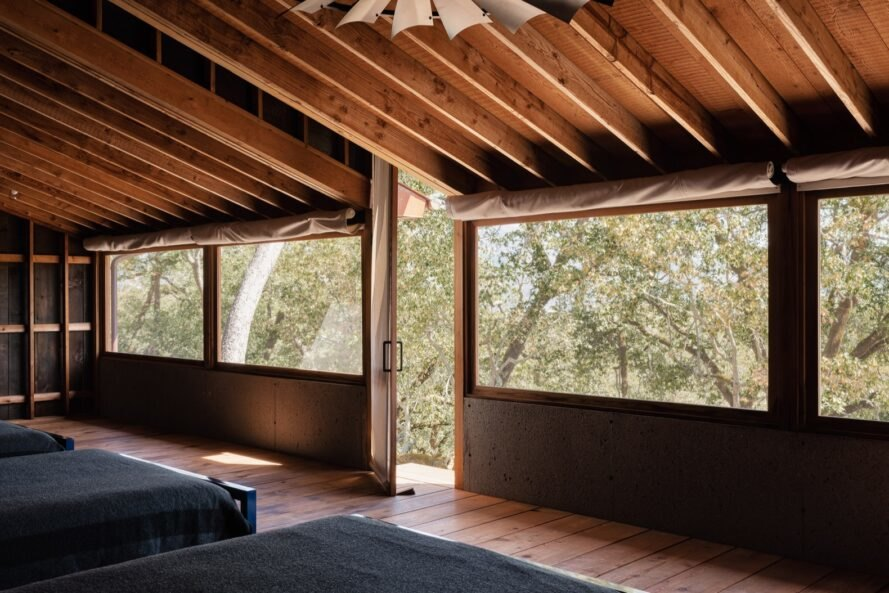 gray beds facing large windows in wood room