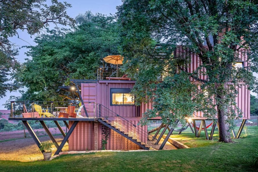 red corrugated metal shipping containers stacked into a house