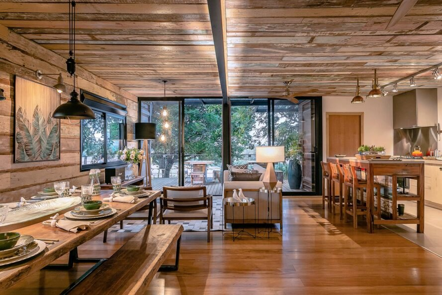 wood-lined, open-plan living space with long wood dining table and beige sofa