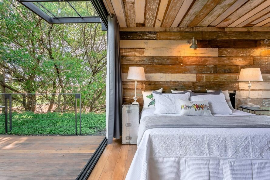 large white bed in wood-lined room with operable glass wall