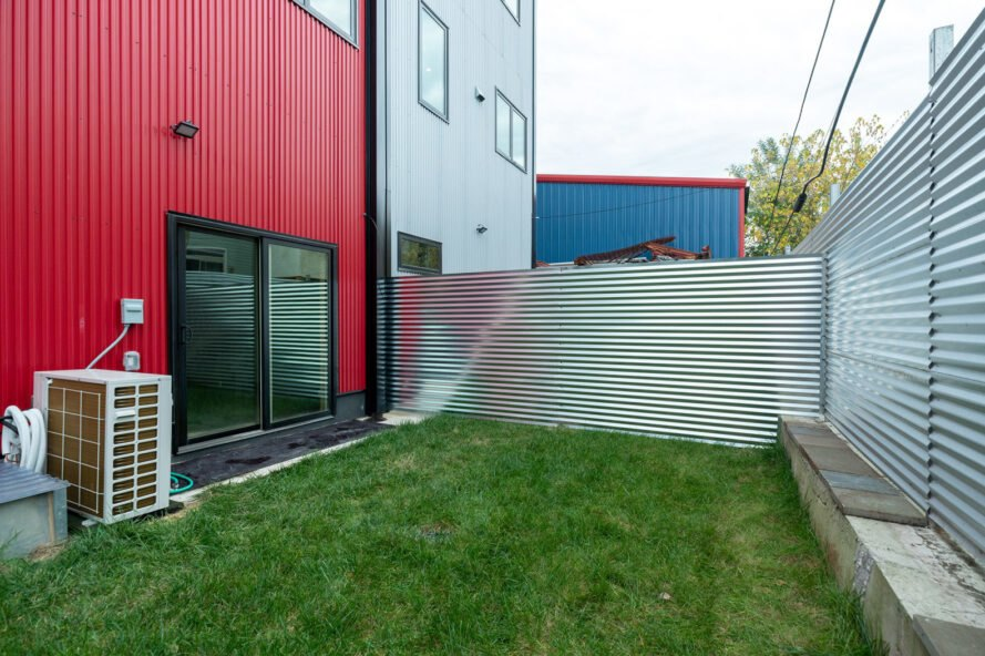 small green yard with corrugated metal fencing