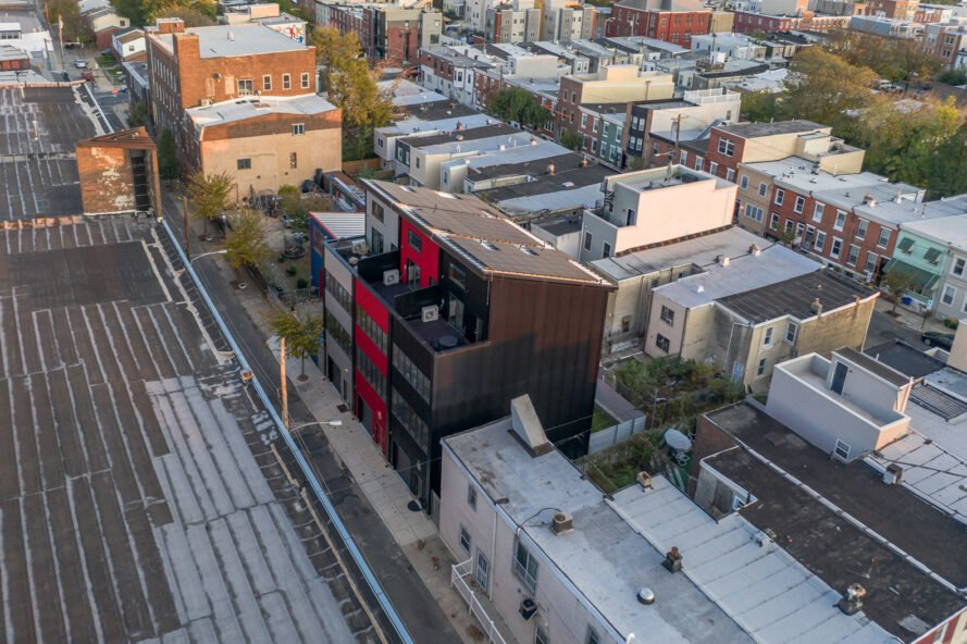 black, gray and red townhomes topped with solar panels in a city