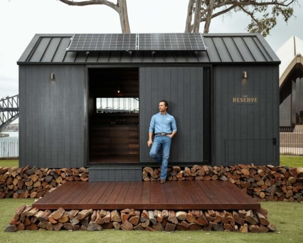 Matthew McConaughey standing in front of a dark tiny cabin