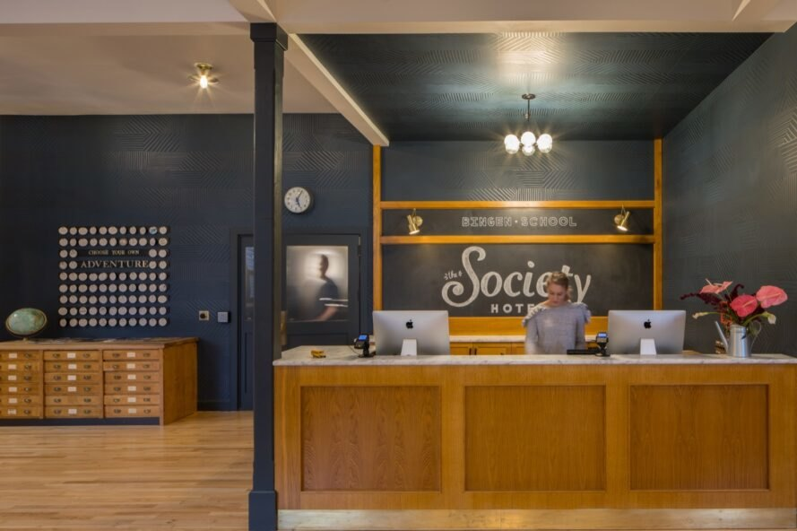 hotel reception area with dark walls and a wood desk