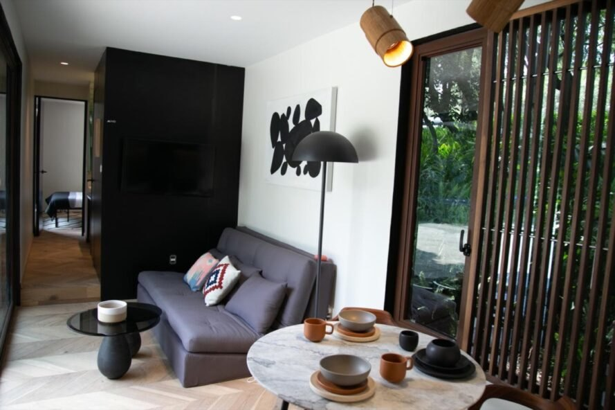 small gray sofa between a hallway and a dining set