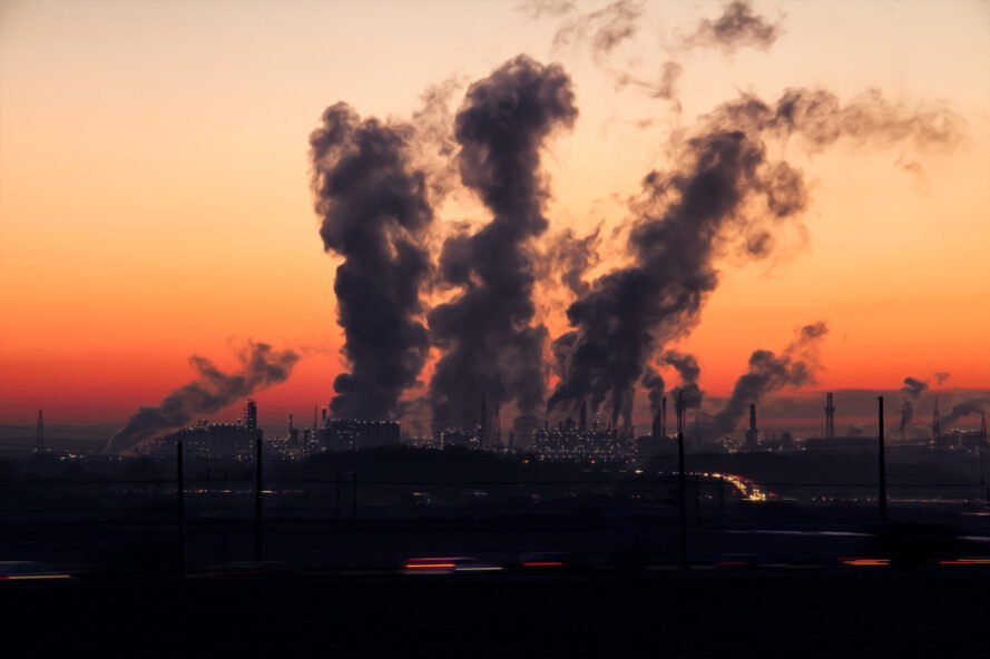 an image of the horizon at sunset with factories in the background producing clouds of exhaust