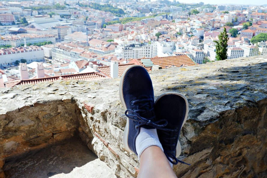 feet in blue sneakers propped up on rock with city views below