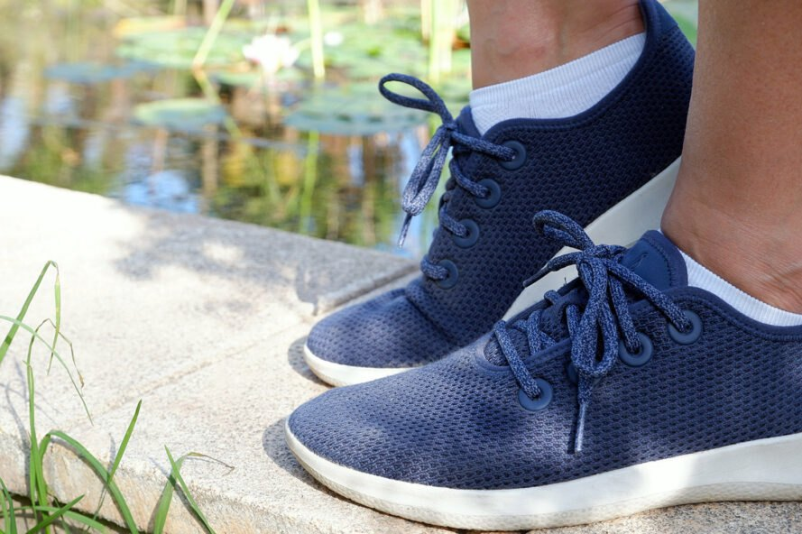 feet in blue sneakers standing on a ledge near a pond