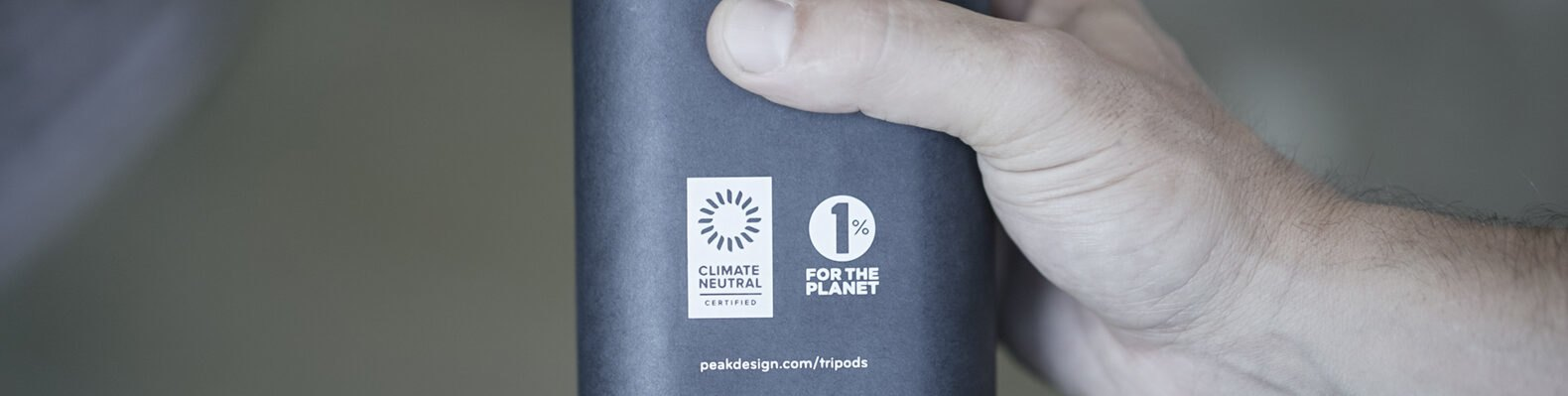 person holding container with logos for Climate Neutral Certification and 1% for the Planet