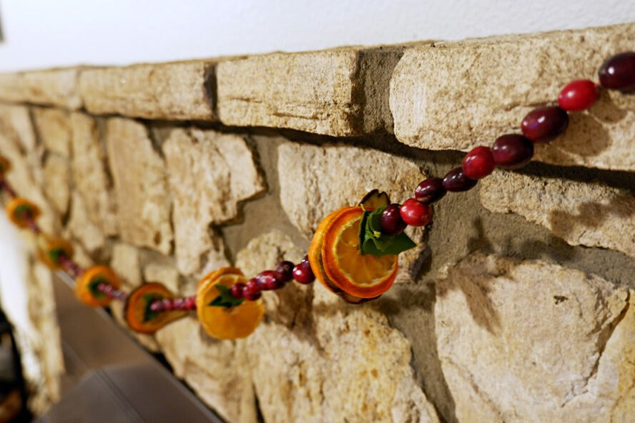garland of dried oranges and cranberry strung from stone fireplace