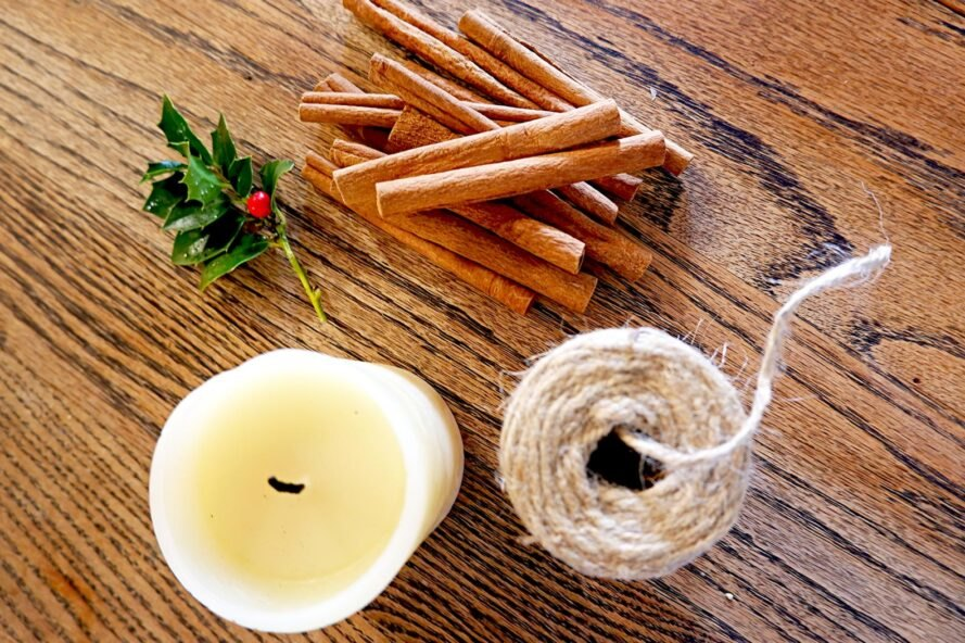 flat lay of candle, twine, holly and cinnamon sticks