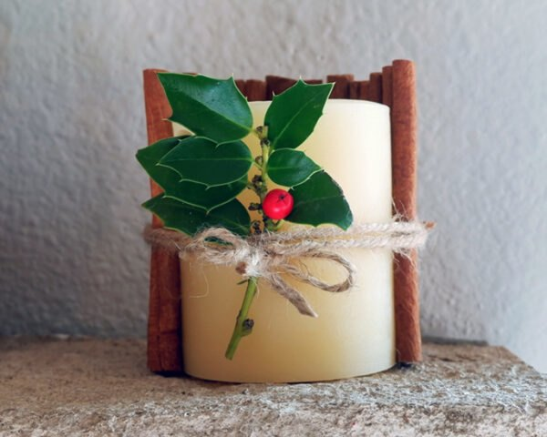 candle wrapped in twine, holly and cinnamon sticks on a fireplace