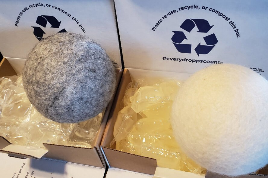 wool dryer balls on top of cardboard boxes filled with laundry pods