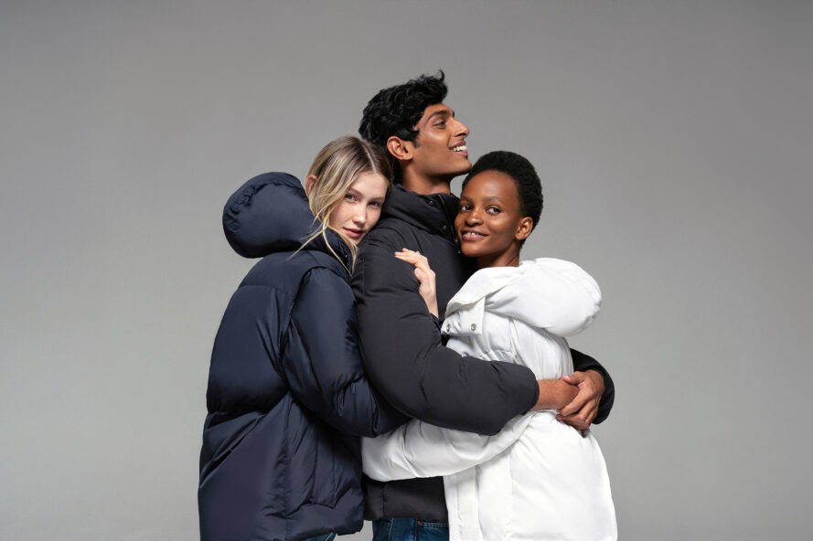 three people wearing puffer coats and hugging