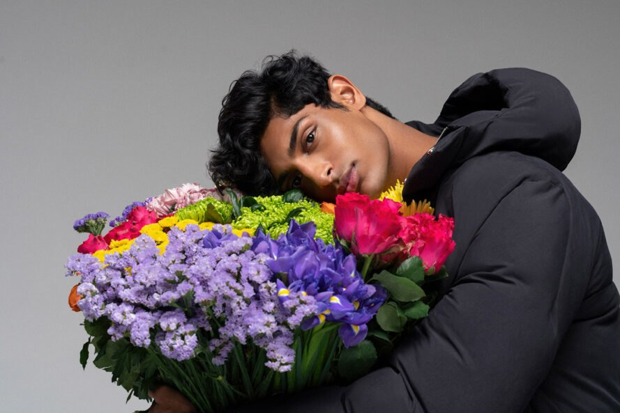 Person wearing puffer coat and smelling multicolored flower bouquet