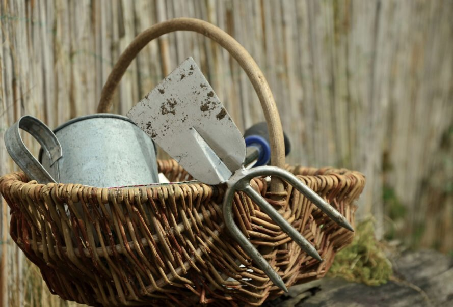metal garden tools in a wicker basket