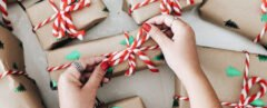 person tying red bows on brown paper-wrapped gifts