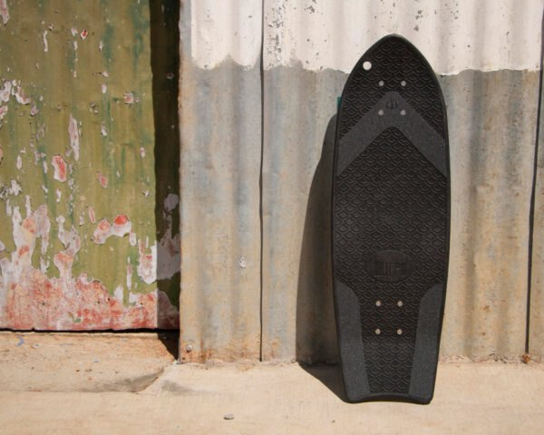 black skateboard leaning on a wall