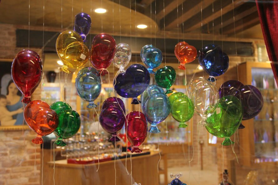 delicate glass-blown balloons hanging on strings in a shop