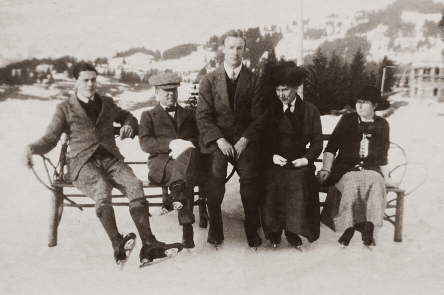 a black and white image featuring a group of five people wearing ice-skates, sitting on a bench in the snow