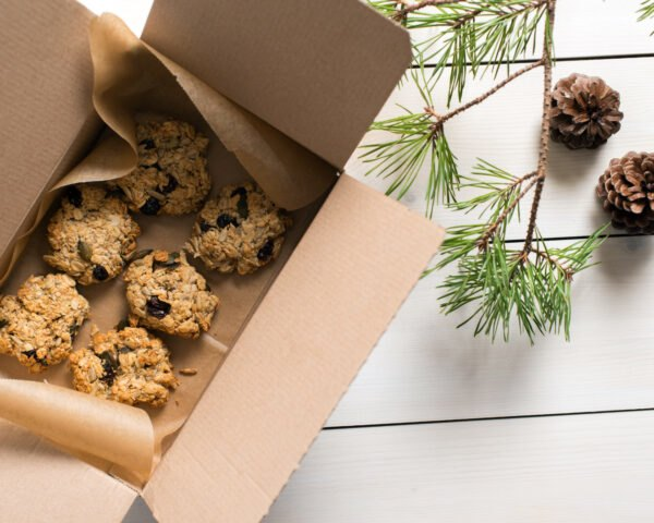 Aerial view of oatmeal raisin cookies in a box near evergreen tree branches