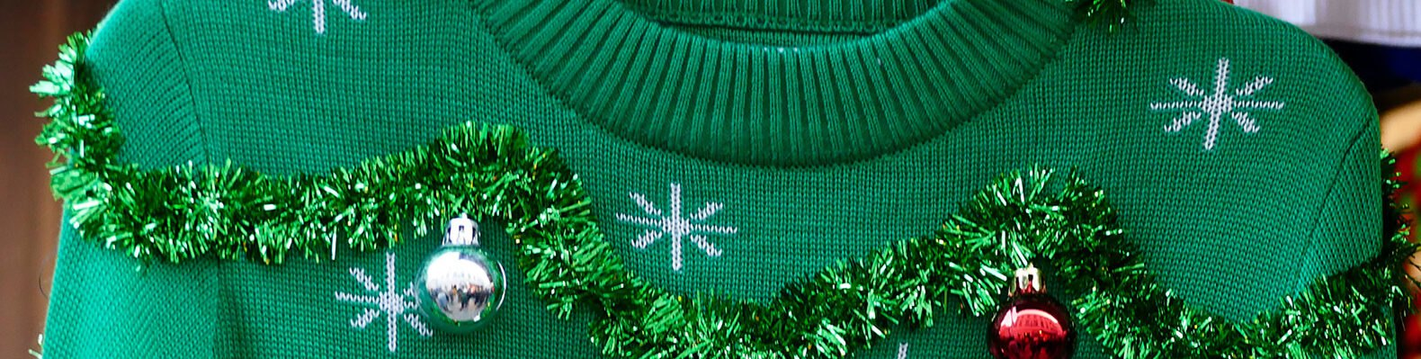 green sweater covered in tinsel and ornaments
